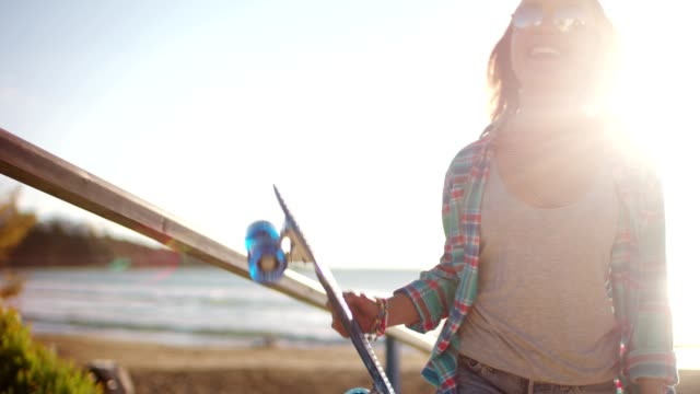 vídeos de stock, filmes e b-roll de menina de skatista hipster jovem andando com skate na praia - viagem de primeira classe
