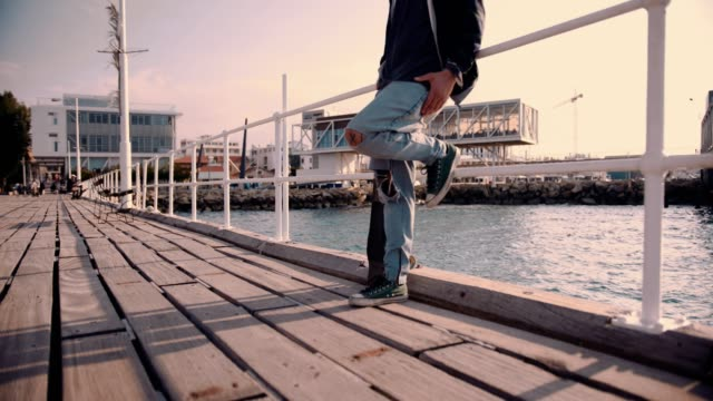 Skateboarder joven inconformista en muelle de madera en la ciudad - vídeo