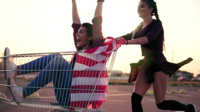 young hipster teen girls having fun at the shopping mall parking, riding in shopping cart holding the american flag. lens flare. slowmotion shot - icona supermercato video stock e b–roll