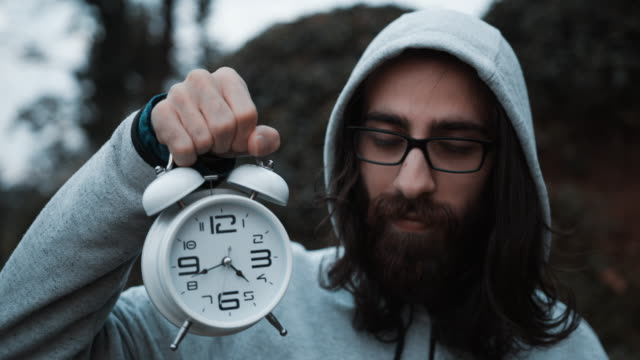 Young hipster with long hair wearing hoodie glasses and holding a white alarm clock in hand. It's 4:40. Time concept.