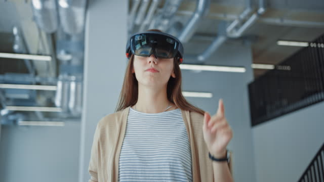 young hipster woman in holographic augmented reality glasses standing in empty office and map it. she's moving virtual pieces around the space. room has tracking points for video software. - rzeczywistość witrualna filmów i materiałów b-roll