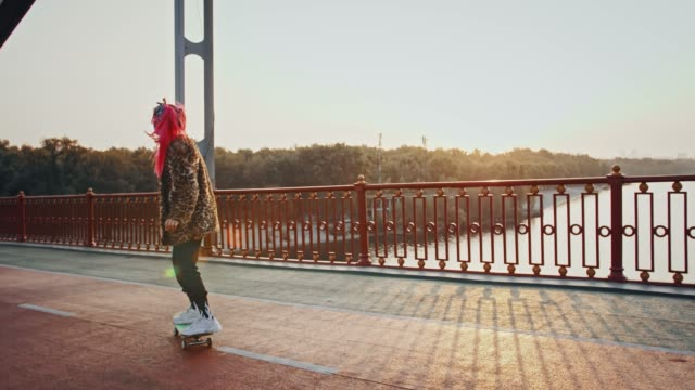 young hipster woman with pink hair, in informal outfit and protective mask is skateboarding on deserted bridge - termine sportivo video stock e b–roll