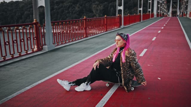 Young hipster woman with pink hair, wearing informal clothes is sitting sideways on skateboard posing on bridge