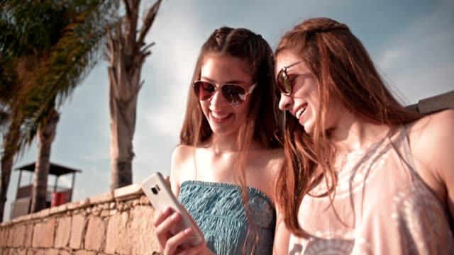 Young hipster women having fun reading text message at beach