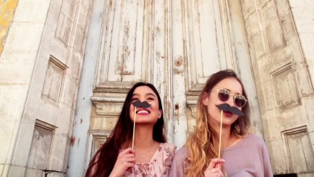 Young hipster women having fun with fake mustaches on sticks video