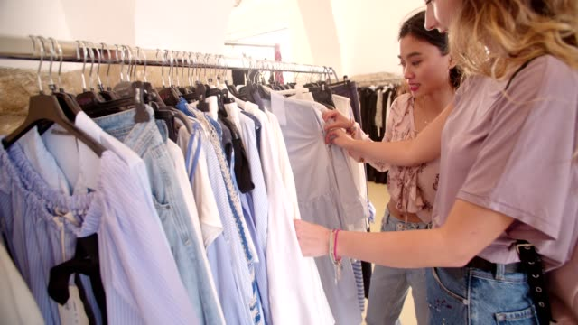 Young hipster women shopping clothes in store at the mall Hipster multi-ethnic teen girls having fun and shopping for clothes in a clothing boutique clothing stock videos & royalty-free footage
