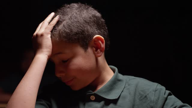 Young hispanic boy sitting at desk, he puts his hand to his head room goes dark