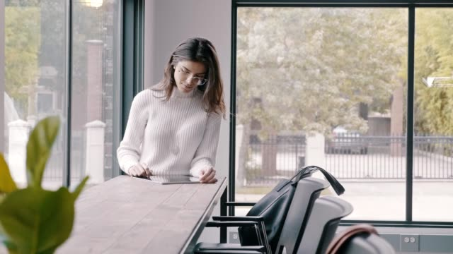 A young Hispanic businesswoman uses a digital tablet in open concept office