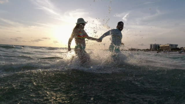 young hispanic couple having fun in the beach at sunset - gulf coast states stock videos & royalty-free footage