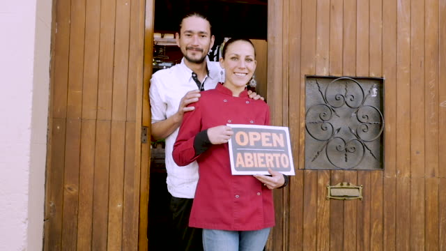 Young Hispanic couple holding a bilingual open sign in front of their business