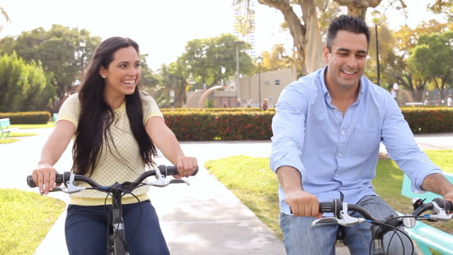 Young Hispanic Couple Riding Bikes In Park video