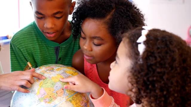 vídeos de stock, filmes e b-roll de professor de creche de jovens latino-americanos ajuda os alunos a estudar um globo - país área geográfica