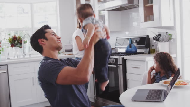 young hispanic family in their kitchen, mum cooking at hob, dad lifting baby in the air, close up - family home video stock e b–roll