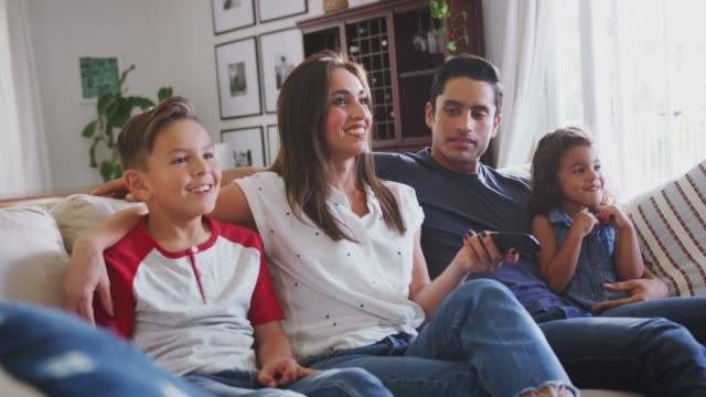 Young Hispanic family sitting on the sofa at home watching TV together, close up Young Hispanic family sitting on the sofa at home watching TV together, close up latin american and hispanic ethnicity stock videos & royalty-free footage