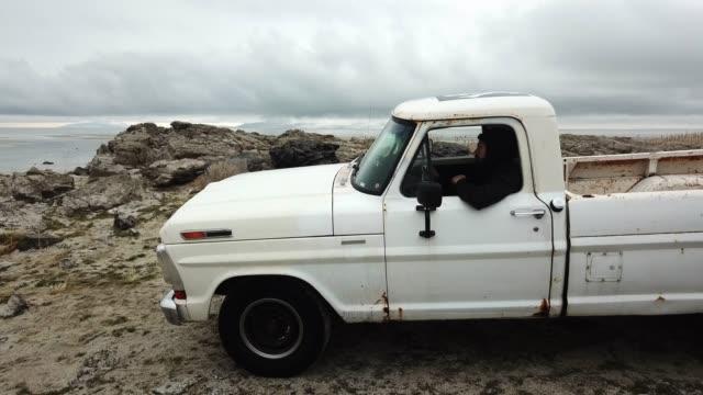 vídeos de stock, filmes e b-roll de homem latino-americano novo na borda da água com seu coletor do vintage - caminhonete pickup