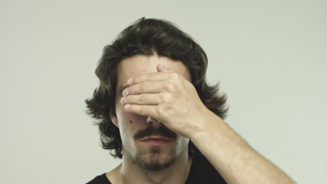 Young hispanic man gesturing see no evil Close up video of young hispanic man covering his eyes with his hands. Footage of real man gesturing see no evil against gray background. Studio 4K RAW video with sharp focus on eyes. ignoring stock videos & royalty-free footage