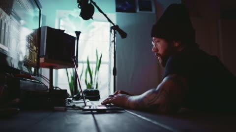 vidéos et rushes de un jeune homme hispanique dans la trentaine avec une barbe, des tatouages, et une boucle d'oreille fonctionne à un ordinateur portable tout en parlant quelqu'un d'autre à côté de l'équipement d'enregistrement de musique dans un studio d'enregistrement - bureau ameublement