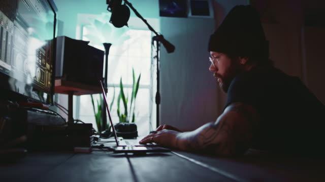 en ung spansktalande man i trettioårsåldern med skägg, tatueringar och ett örhänge fungerar på en bärbar dator medan talking någon annan bredvid musikinspelningsutrustning i en inspelningsstudio - latino music bildbanksvideor och videomaterial från bakom kulisserna