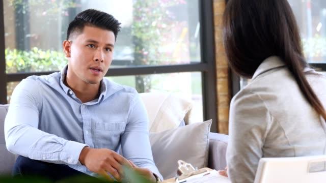 vídeos de stock e filmes b-roll de young hispanic man talks with female therapist - homens jovens