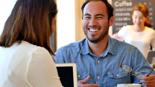 若いヒスパニック男の仕事の前にカフェで友人と会談します。 ビデオ