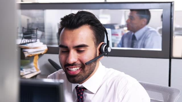 vídeos de stock, filmes e b-roll de homem de jovens latino-americanos a trabalhar em um centro de chamada de serviço ao cliente - call center