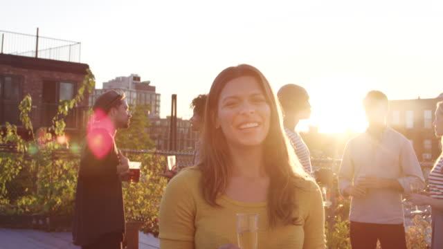 vídeos de stock e filmes b-roll de young hispanic woman at a rooftop party smiling to camera - telhado