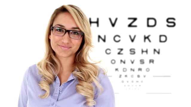 Young Hispanic Woman in Eyeglasses with Eye Exam Chart HD footage of an attractive young Hispanic woman putting on eyeglasses with an eye exam chart in the background. eye chart stock videos & royalty-free footage
