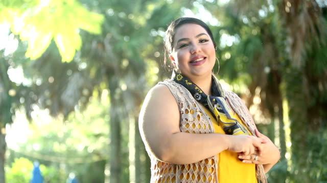 young hispanic woman in park on sunny day - dbałość o ciało filmów i materiałów b-roll
