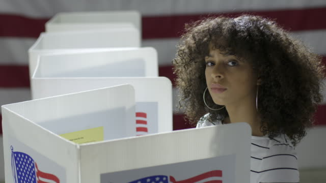 Young Hispanic woman looks up from voting at booths at polling station video