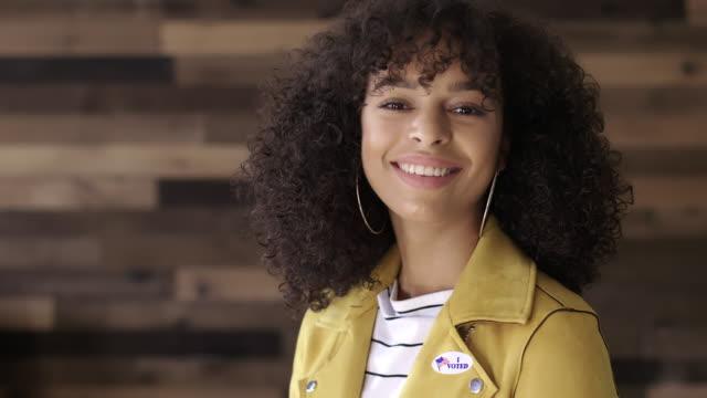 vídeos y material grabado en eventos de stock de mcu joven hispanic mujer se pone i votado pegatina y sonrisas - polling place