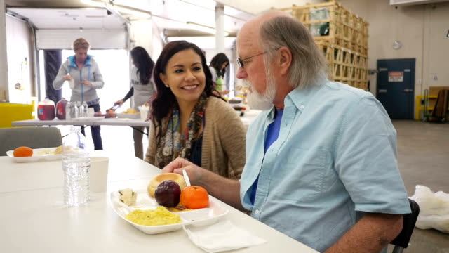 Young Hispanic woman volunteering to assist seniors in community soup kitchen Young Hispanic woman volunteering to assist seniors in community soup kitchen homelessness stock videos & royalty-free footage