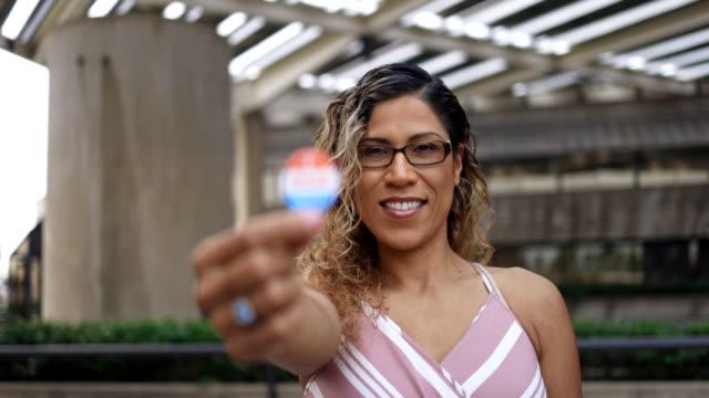 junge hispanische frau mit ich wählte aufkleber - aufkleber stock-videos und b-roll-filmmaterial