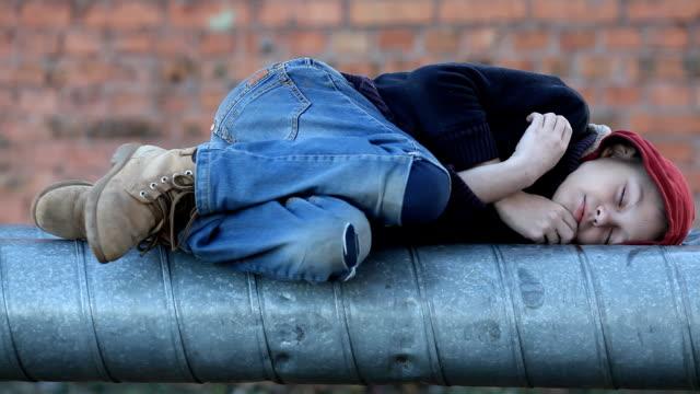 hemlös pojke som sover på en värme-pipe - cold street bildbanksvideor och videomaterial från bakom kulisserna