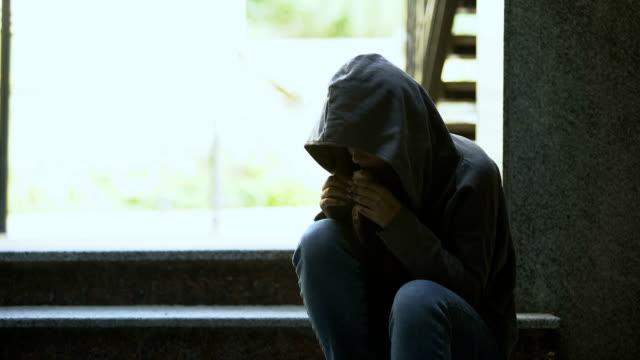 молодая бездомная женщина в толстовке ест бутерброд на открытом воздухе, бедность и проблемы - голодный стоковые видео и кадры b-roll