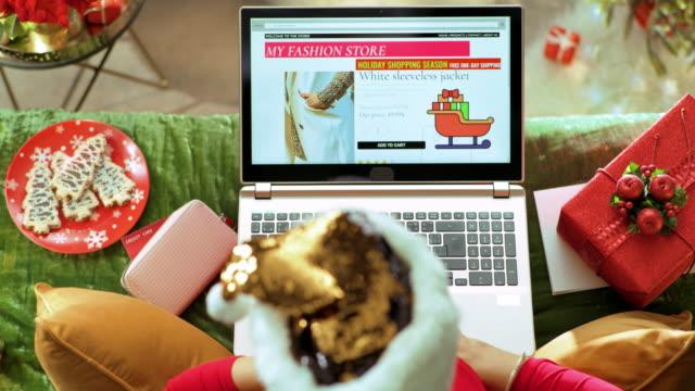 vídeos y material grabado en eventos de stock de joven ama de casa comprando ropa en línea en la computadora portátil - advent