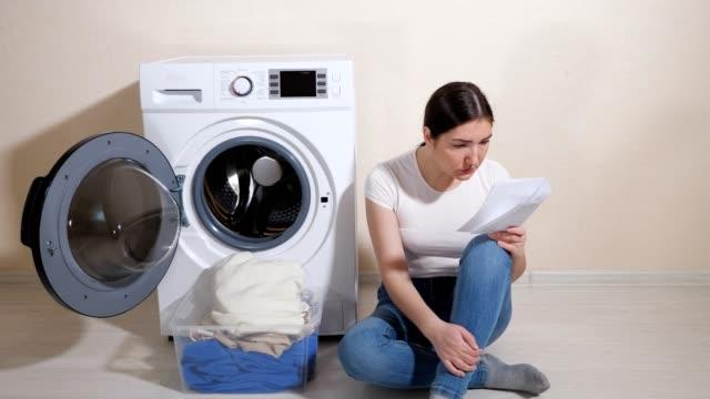 junge hausfrau in jeans lernt einstellungen der neuen waschmaschine mit unterricht - waschmaschine wand stock-videos und b-roll-filmmaterial
