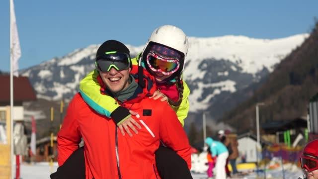 ung man och hustru, pojkvän och flickvän har kul på en skidort. vinter aktiviteter, skidutrustning - vintersport bildbanksvideor och videomaterial från bakom kulisserna