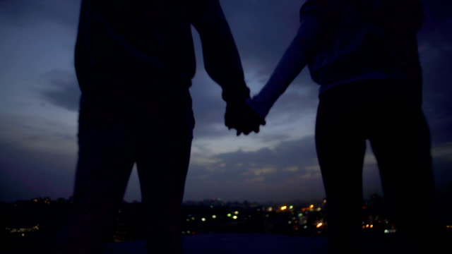 Young husband and wife enjoying moments of solitude, illuminated city at night video