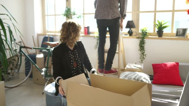 Young husband and wife unpacking in new apartment video