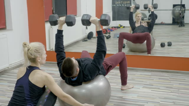 Young husband exercising on a pilates ball with dumbbells to recover after surgery while being helped by her beautiful slim wife video