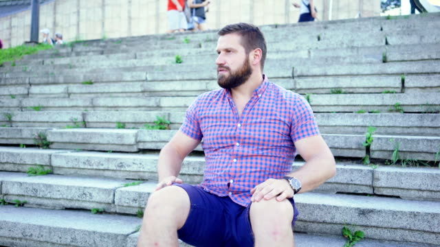 Young impatient man sitting on stairs waiting for someone, slider shot. Young impatient man sitting on stairs waiting for someone, slider shot. He is dressed in blue shorts and checkered shirt. He has beard. impatient stock videos & royalty-free footage