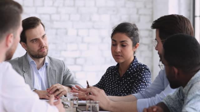vídeos de stock e filmes b-roll de young indian businesswoman negotiating with diverse businessmen at office table - envolvimento dos funcionários