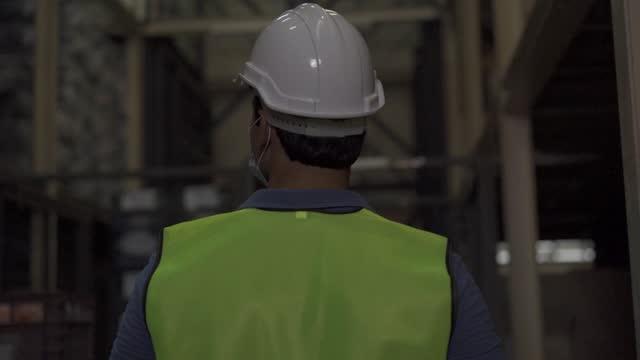 giovane magazziniera indiana che indossa una maschera protettiva per il viso e un casco di sicurezza mentre lavora nell'industria logistica indoor. 30s uomo controllo ordine di magazzino durante coronavirus covid 19 pandemia - dorso umano video stock e b–roll