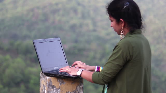 Young Indian girl using laptop outdoors in mountains, Himachal Pradesh, India video