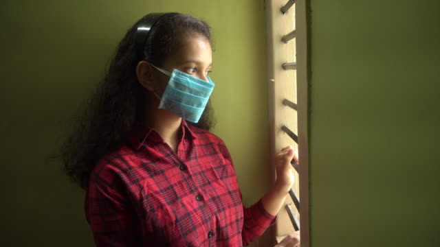 Young Indian girl wearing a medicine mask and looking outside video