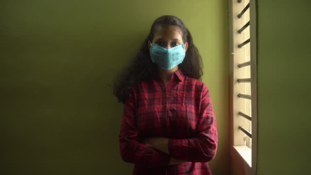 Young Indian girl wearing a medicine mask and standing near the window video