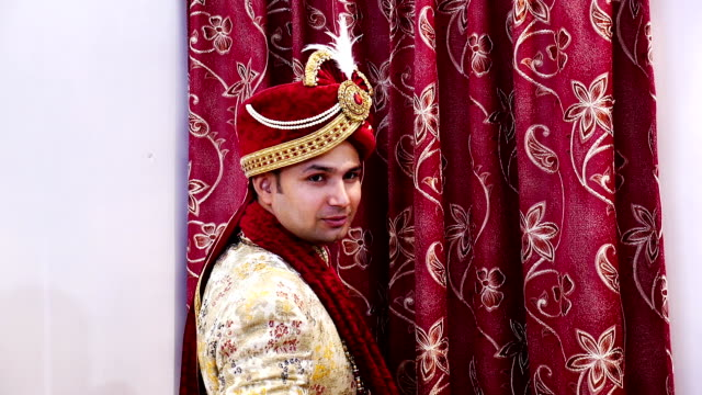 Young Indian groom posing for photographer on wedding day video