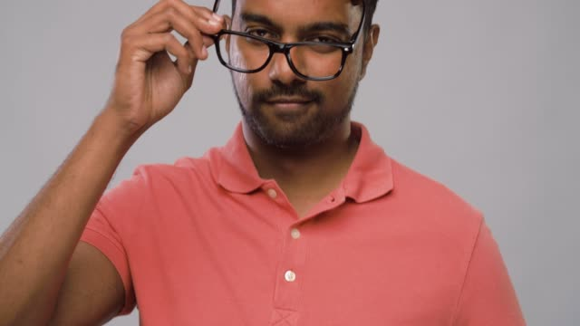 young indian man in glasses touching his hair