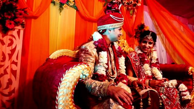 Jovem casal indiano sentado em sofá de luxo ambos conversando um com o outro no palco do casamento - vídeo