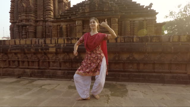 Young Indian woman dances traditional Odissi style in front of ancient temple